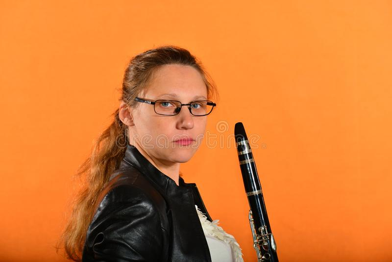 A girl with glasses in a black jacket holds a clarinet in her hands and looks into the camera, on a yellow background.  stock photography