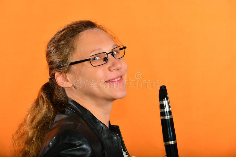 A girl with glasses in a black jacket holds a clarinet in her hands and looks into the camera, on a yellow background.  royalty free stock photos