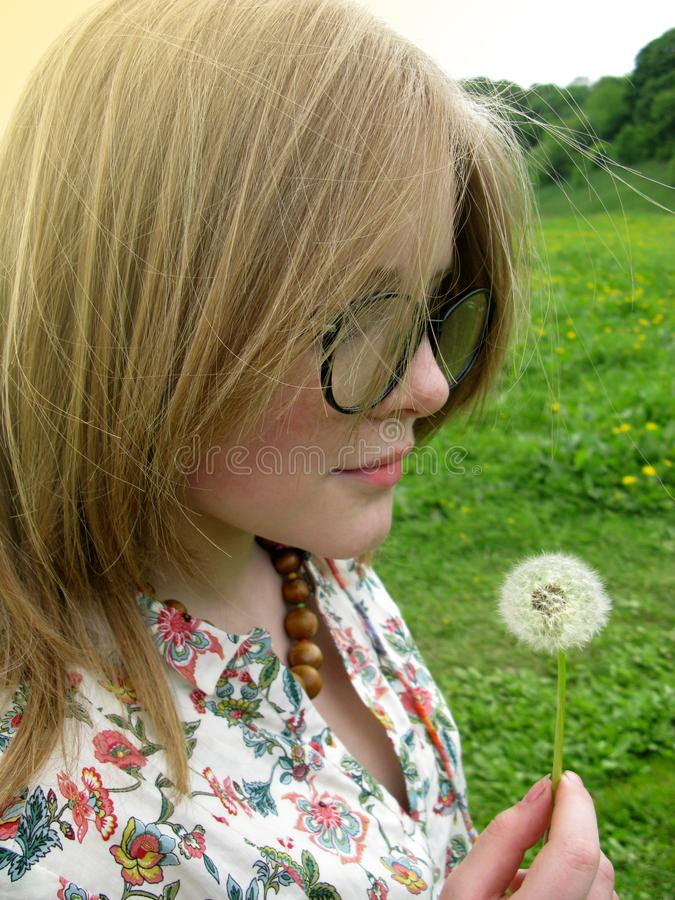 Girl with glasses on the lawn with a dandelion stock photos
