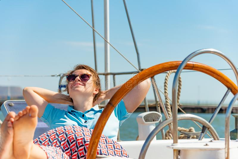 A girl in glasses sits near the wheel next to on the deck of a yacht looking around. royalty free stock photos