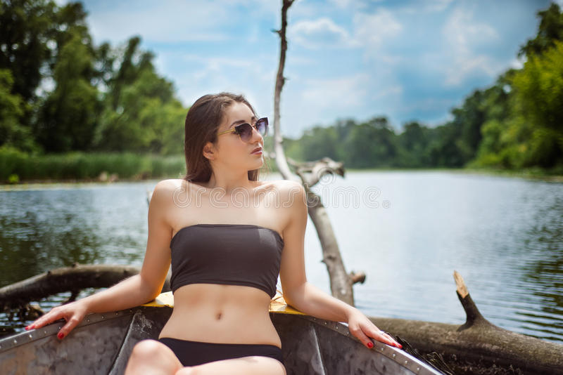 Girl in glasses sitting at the boat. Brunette young girl in glasses sitting in the boat with sky background stock photography