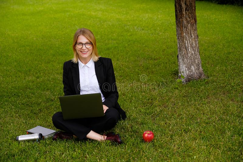 Girl with glasses sitting on the grass, working on a laptop, looking at the camera, smiling. A mobile phone, a thermos, an Apple. royalty free stock photos