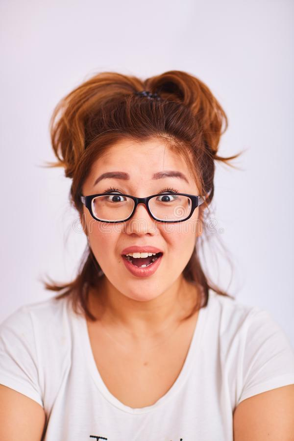 A girl in glasses smiles and looks with surprised eyes royalty free stock image