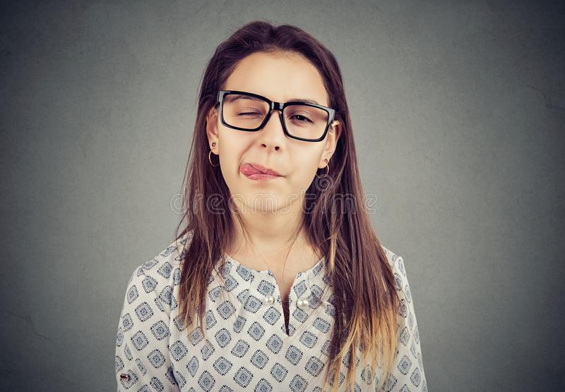 Girl in glasses sticking out tongue. Girl in glasses sticking out her tongue looking at camera stock image
