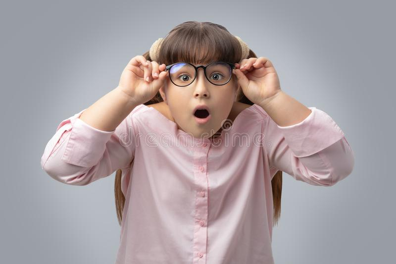 Girl with glasses surprised . disciple shocked. gray background . stock photos