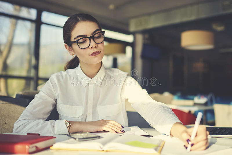 Girl in glasses working to continue education on stipend working learning new information in campus royalty free stock image