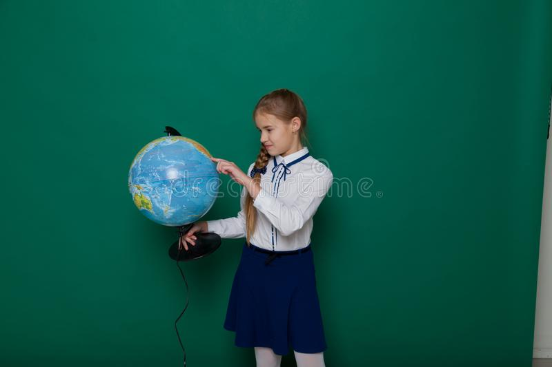 Girl with a globe at the Blackboard in a class lesson stock photography