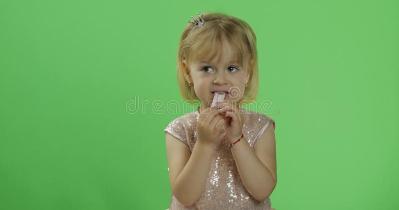 Girl in glossy dress begins to eat chewing gum. Happy child. Chroma Key. Girl in glossy dress begins to eat chewing gum candy. Happy four years old girl. Pretty stock photos