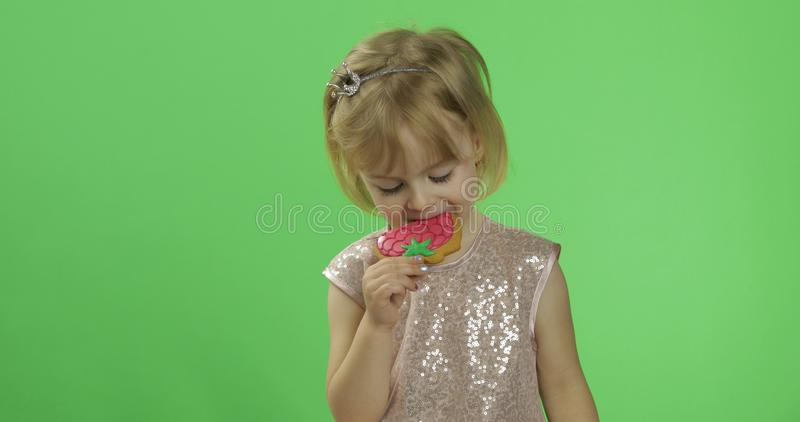 Girl in glossy dress begins to eat cookies in the form of strawberries. Happy four years old girl. Pretty little child, 3-4 year old blonde girl. Make faces stock image