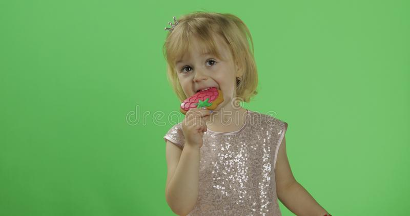 Girl in glossy dress begins to eat cookies in the form of strawberries. Happy four years old girl. Pretty little child, 3-4 year old blonde girl. Make faces stock photos
