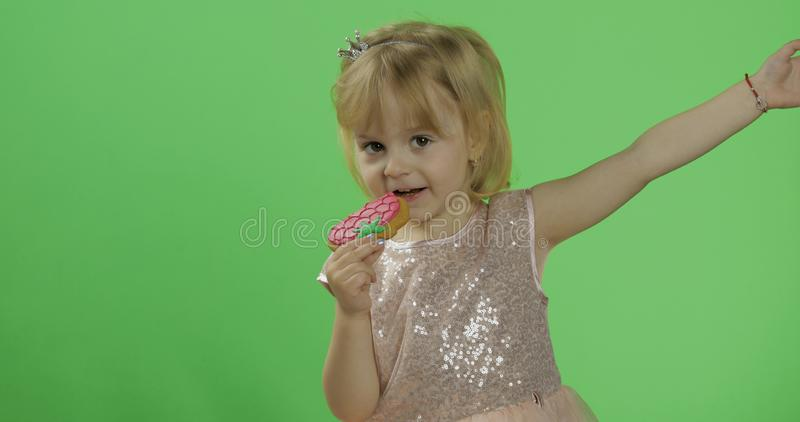 Girl in glossy dress begins to eat cookies in the form of strawberries. Happy four years old girl. Pretty little child, 3-4 year old blonde girl. Make faces royalty free stock photography