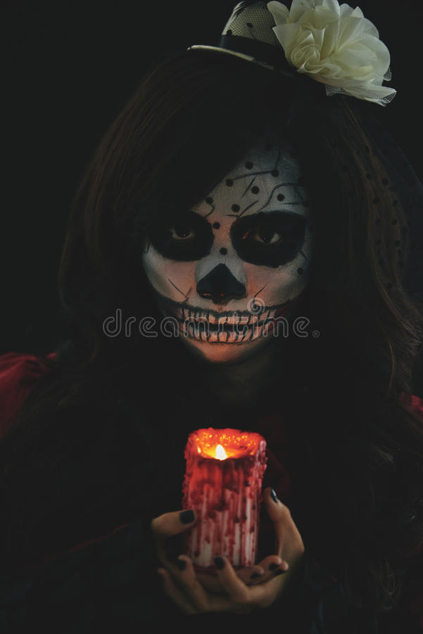 Girl with glowing candle. Scary girl in Halloween costume holding glowing candle stock photography