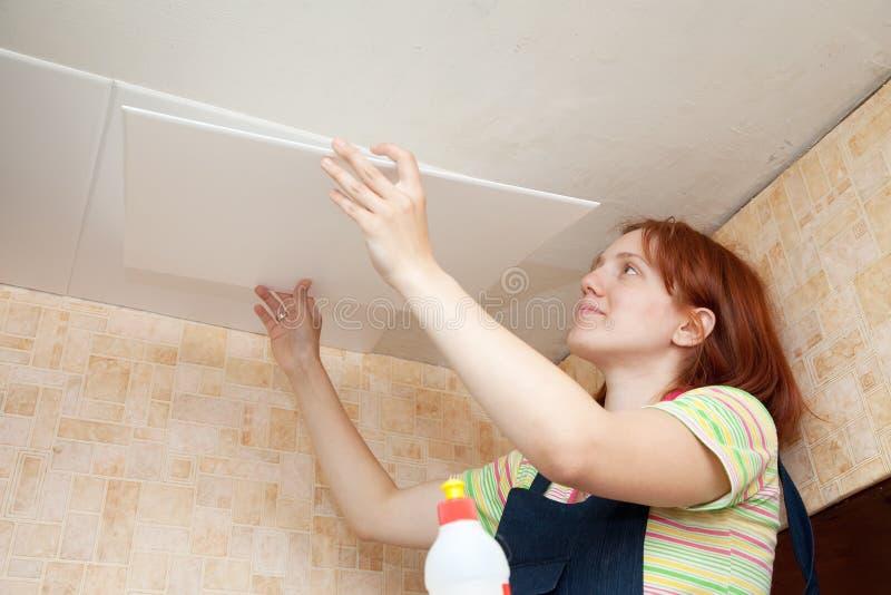 Girl glues ceiling tile royalty free stock photo