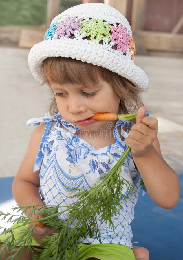 The girl gnaws a carrot royalty free stock photography