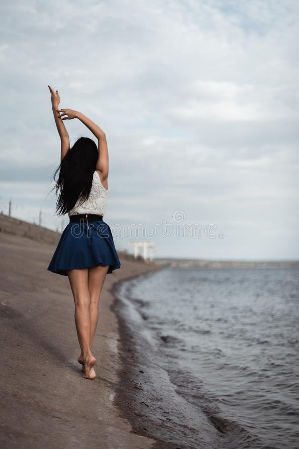 The girl goes along the concrete shore of the hydroelectric power station stock photography