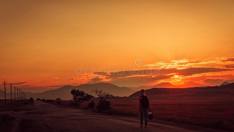 The girl goes on the road at sunset in the mountains royalty free stock photos