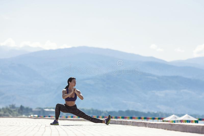 The girl goes in for sports, doing a workout on the waterfront royalty free stock image