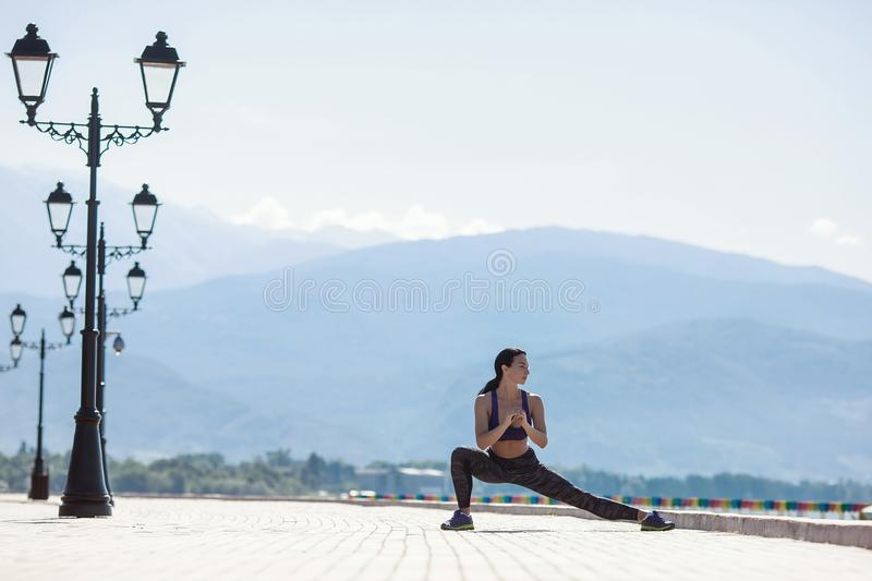 The girl goes in for sports, doing a workout on the waterfront stock image