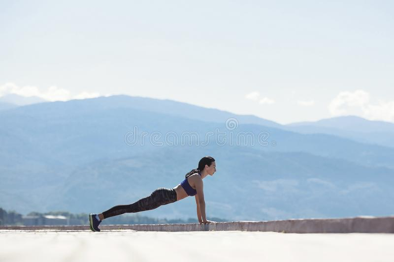 The girl goes in for sports, doing a workout on the waterfront royalty free stock images