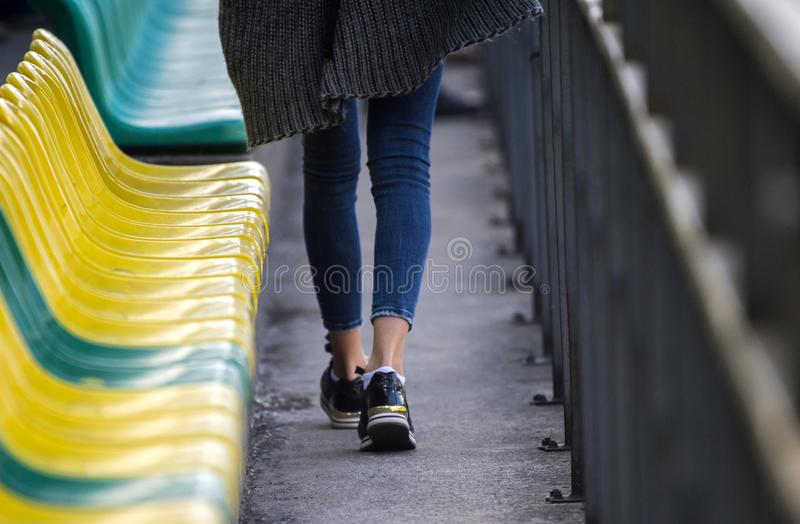 Girl goes to the football game. audience gathering to the stadium stock photos