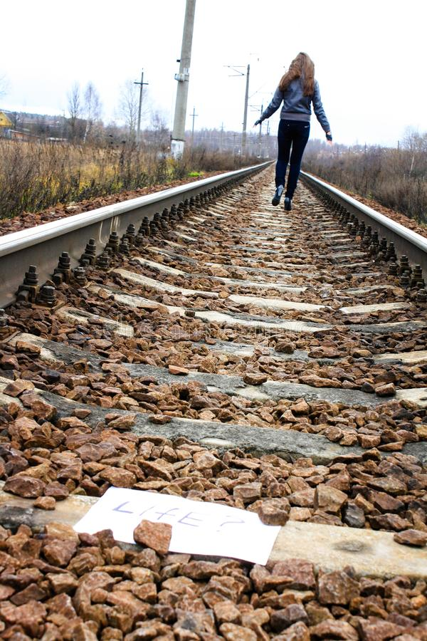 Girl goes on the tracks thinking about life stock photography