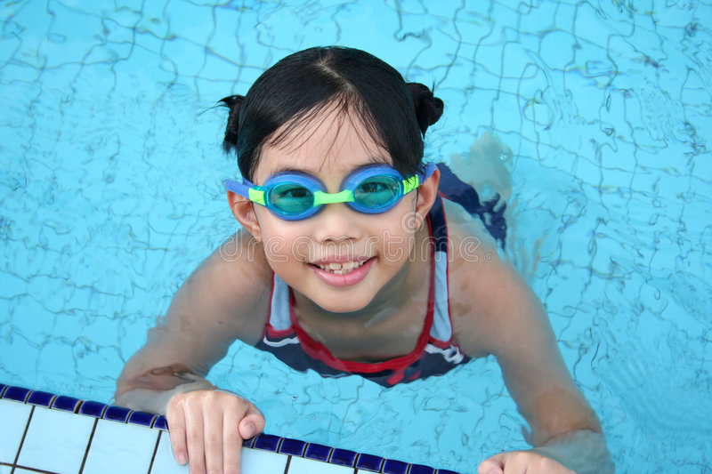 Girl with goggles in the pool stock images