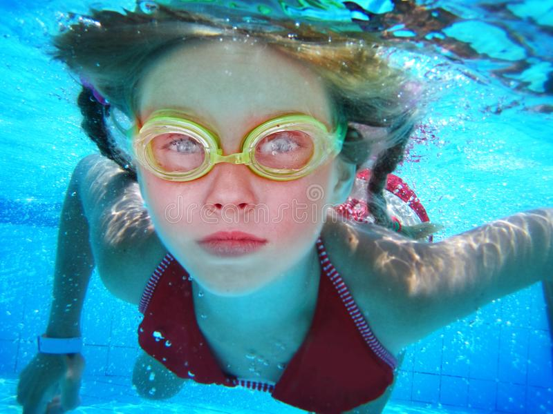 Girl in goggles swim and dive under water. royalty free stock photo