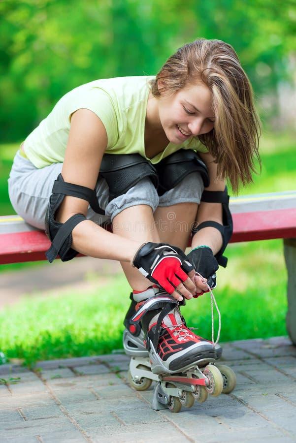 Girl going rollerblading sitting in bench putting on inline skates. Woman skating in park. Girl going rollerblading sitting on bench putting on inline skates royalty free stock photo