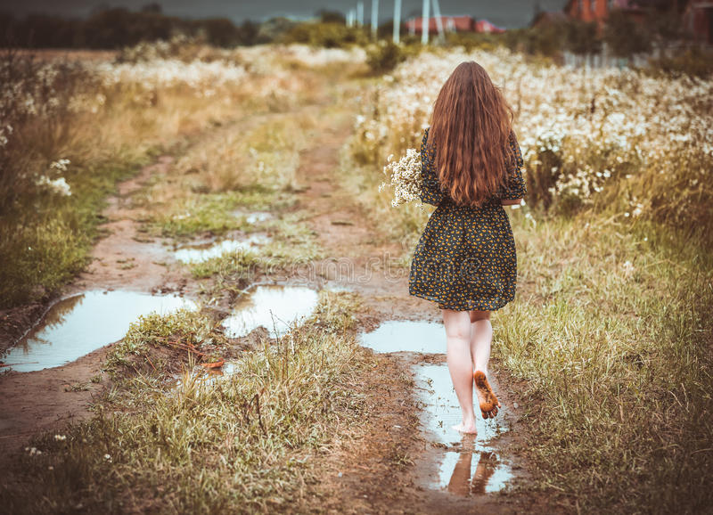 Girl going on rural road. With a bouquet of wild flowers stock images