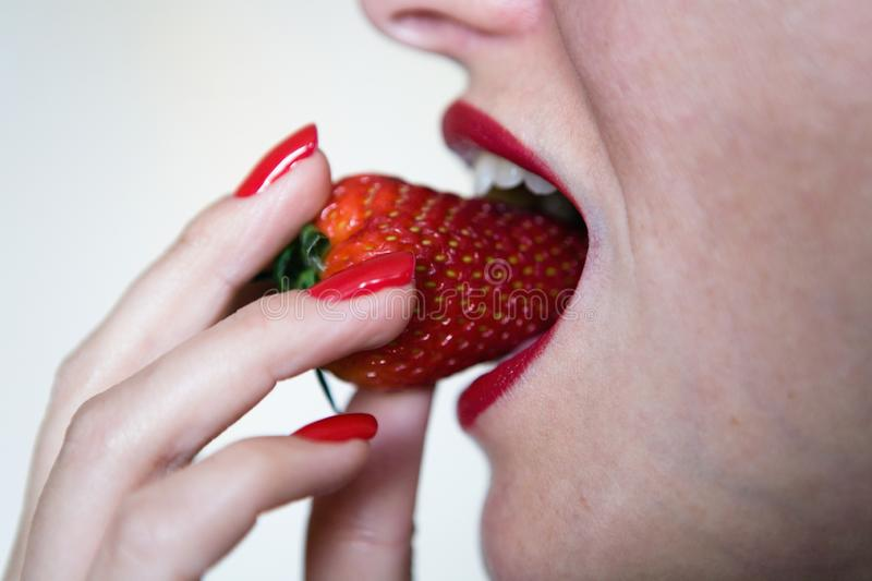 The girl is going to bite off strawberries. royalty free stock photo
