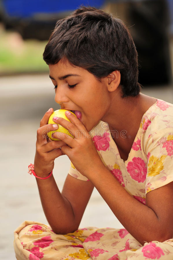 Girl with golden apple. Poor village girl eating golden apple royalty free stock photography
