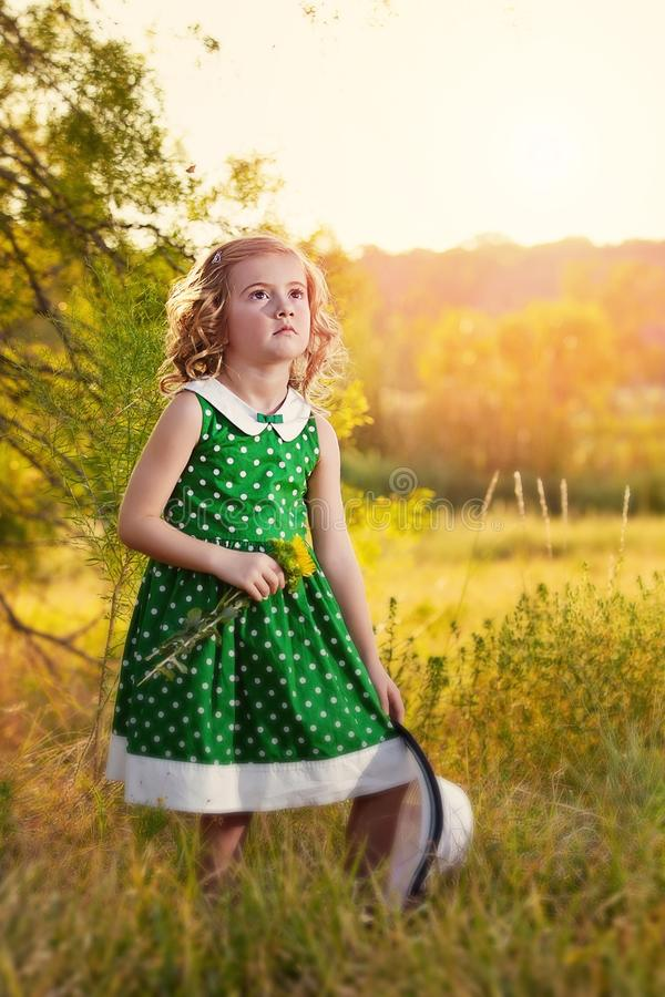 Girl in golden countryside. Pretty blonde girl wearing green and white polka dot dress, holding a straw hat standing beside a tree in golden countryside stock photo