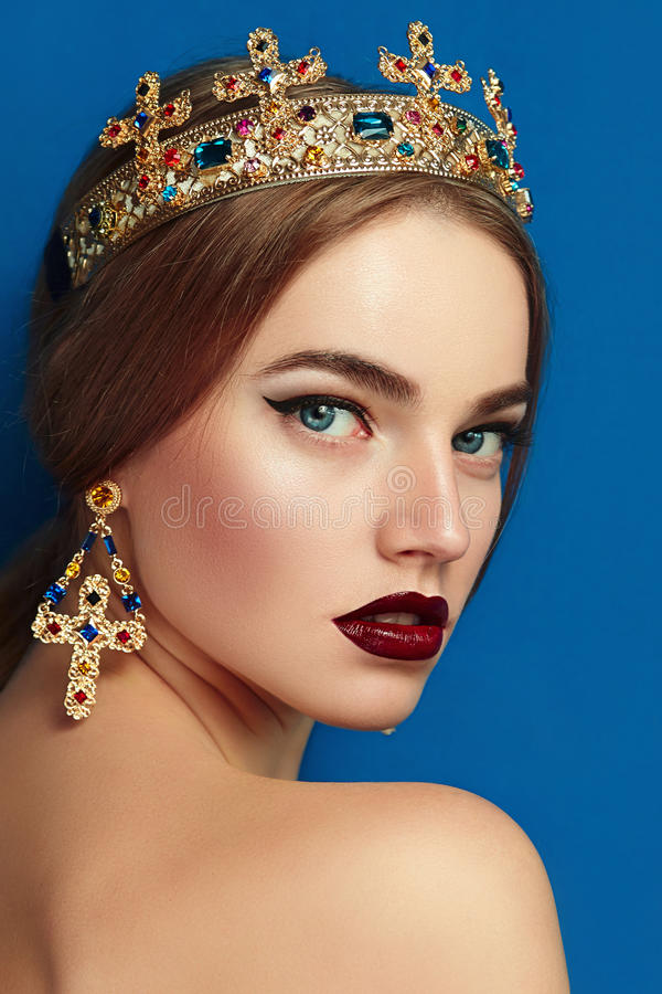 Girl with a golden crown and golden earrings. stock photo