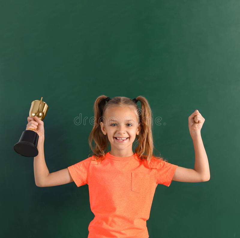 Girl with golden winning cup near chalkboard. Happy girl with golden winning cup near chalkboard royalty free stock photo