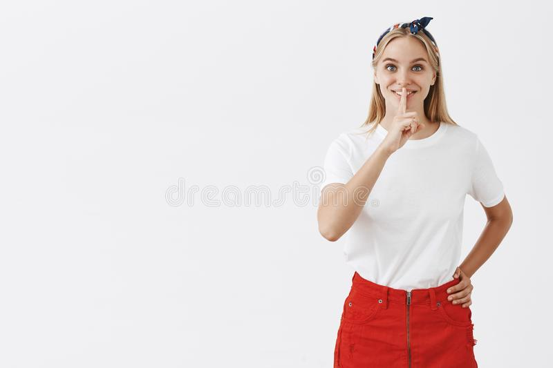 Girl gonna share her beauty secrets so shh. Charming good-looking fit woman in trendy red skirt, holding hand on waist royalty free stock photo