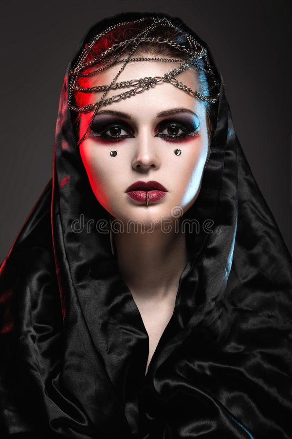 Girl in gothic art style. Girl in gothic art style with creative makeup, black hood and chains stock photos
