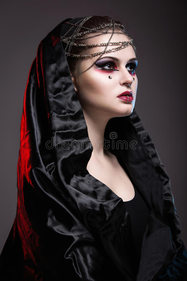 Girl in gothic art style. Girl in gothic art style with creative makeup, black hood and chains stock image