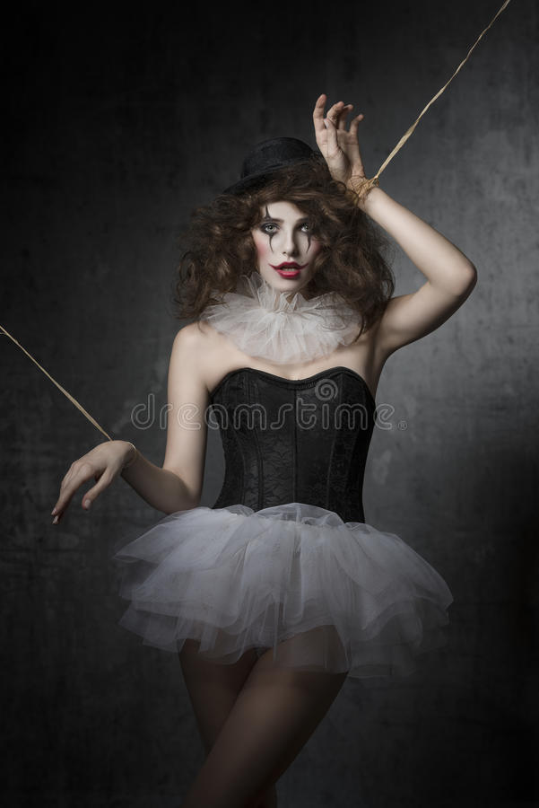 Girl with gothic puppet costume. Bizarre fashion portrait of brunette girl with gothic puppet costume. Wearing tutu, bowler hat and clown make-up. Uncombed hair royalty free stock photography