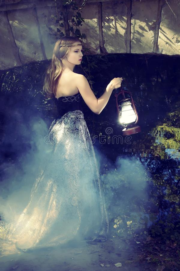 Girl. Gothic girl standing with a lantern in his hand at the bridge stock photography