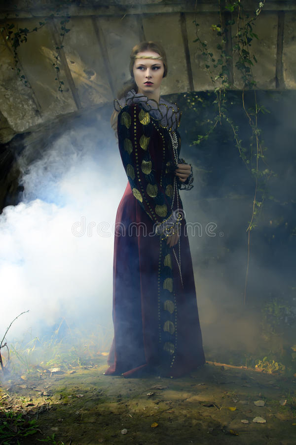 Girl. Gothic girl standing with a lantern in his hand at the bridge royalty free stock photography