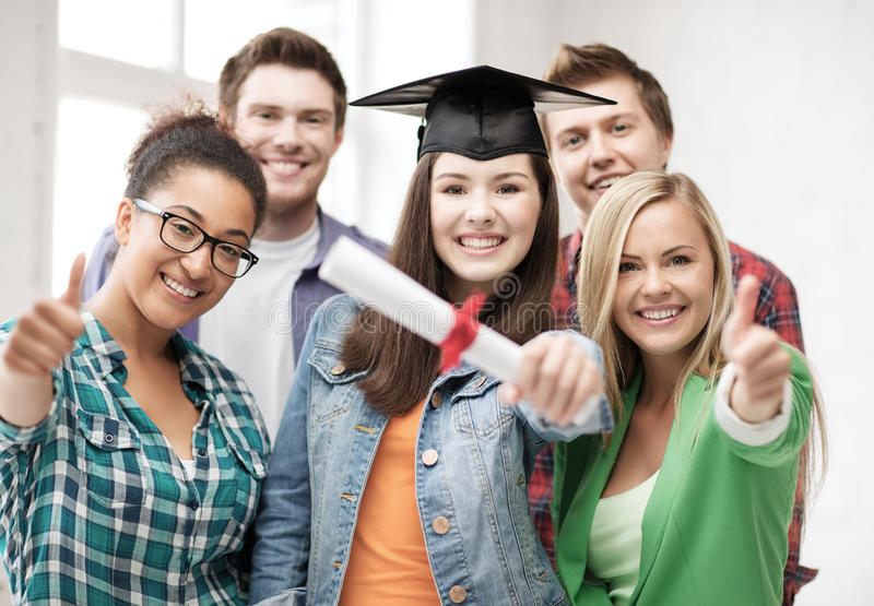 Girl in graduation cap with diploma and students. Education concept - happy girl in graduation cap with diploma and students royalty free stock photos