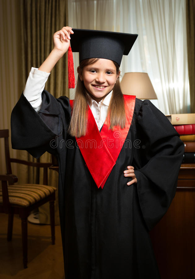 Girl in graduation cap and gown posing at classic interior. Portrait of happy smiling girl in graduation cap and gown posing at classic interior stock images