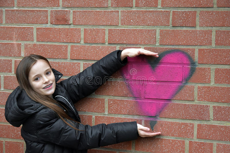 Girl and graffiti heart royalty free stock image