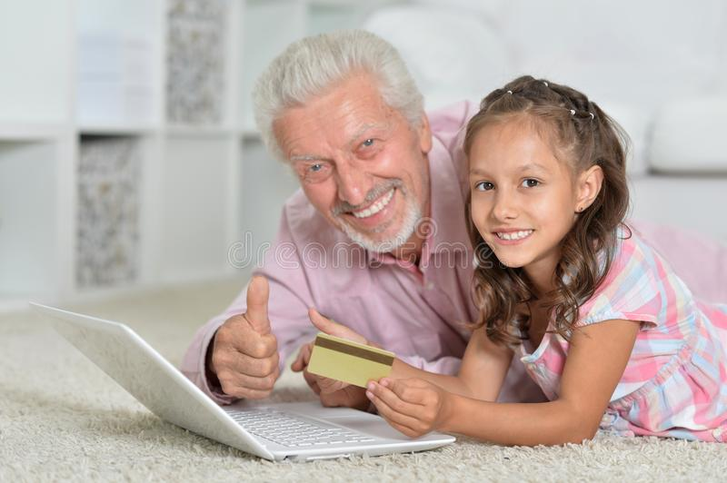 Girl and grandfather with laptop and credit card at home stock images