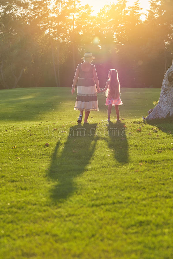 Girl with grandmother, back view. stock photo