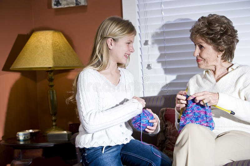 Girl with grandmother knitting at home. In living room stock photography