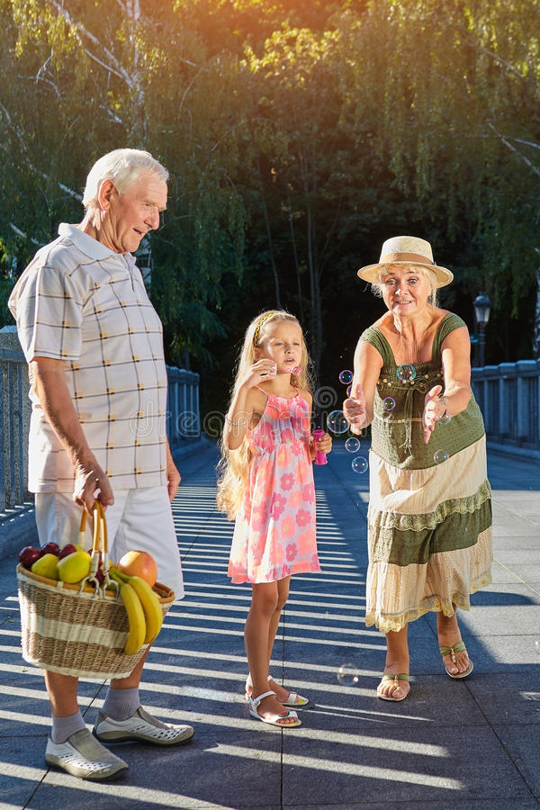 Girl with grandparents, bubble blower. stock photography
