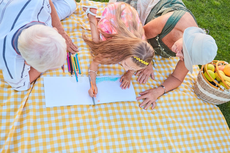 Girl with grandparents drawing. royalty free stock photo
