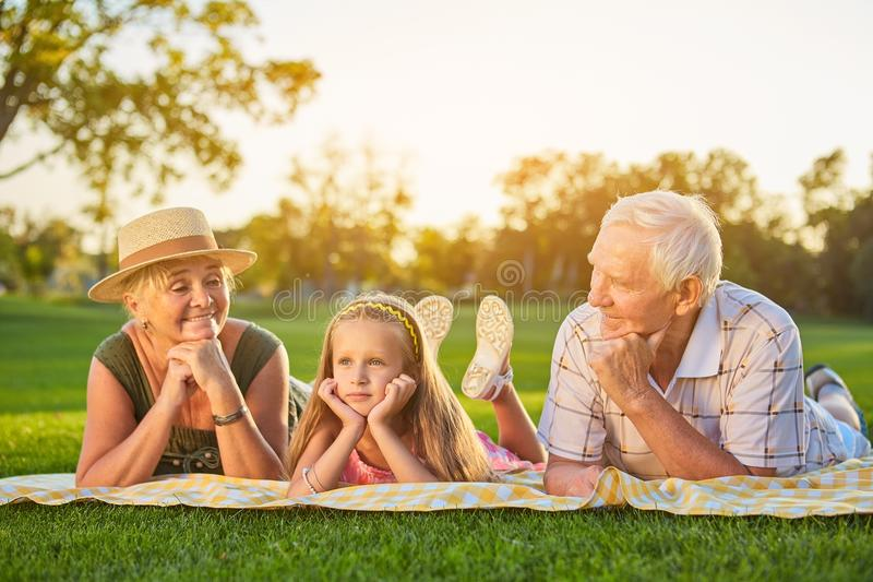 Girl with grandparents lying outdoors. royalty free stock photos