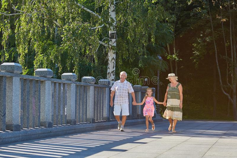 Girl with grandparents outdoors. stock photography